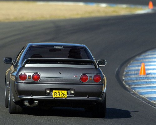 Rear view of silver Japanese supercar on racetrack